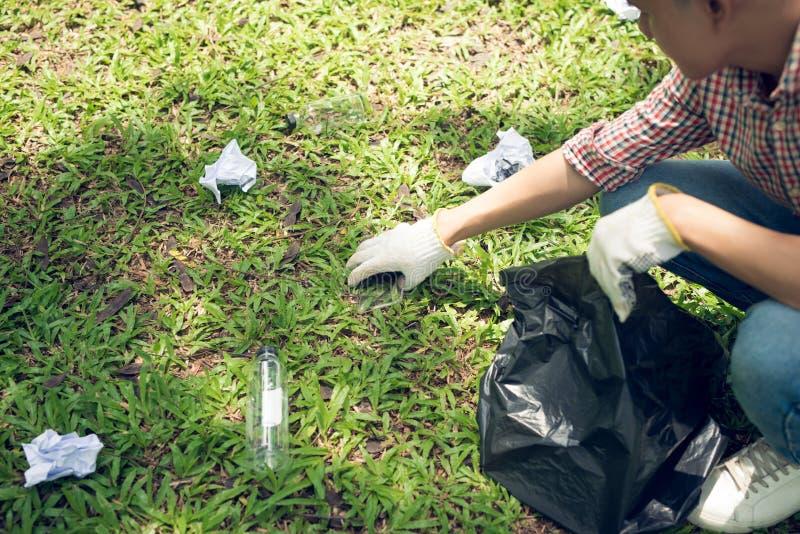 拾起塑料家庭废物的亚裔人在公园 图库摄影