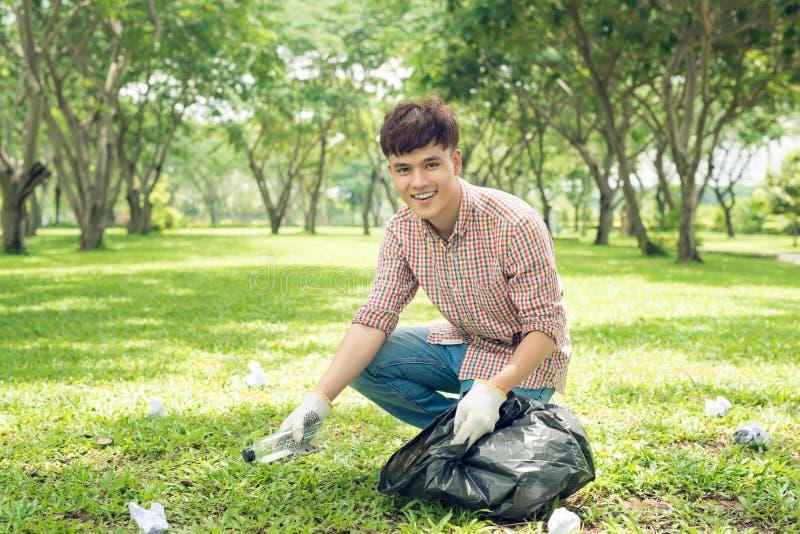 拾起塑料家庭废物的亚裔人在公园 库存照片