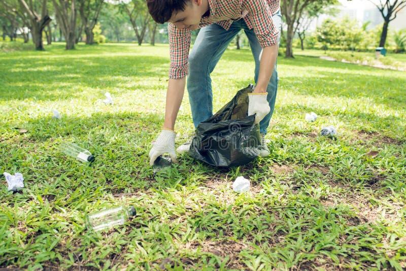 拾起塑料家庭废物的亚裔人在公园 免版税库存照片