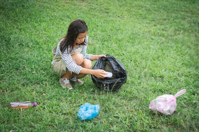 拾起塑料的逗人喜爱的女孩入在公园的容器袋子 免版税库存照片