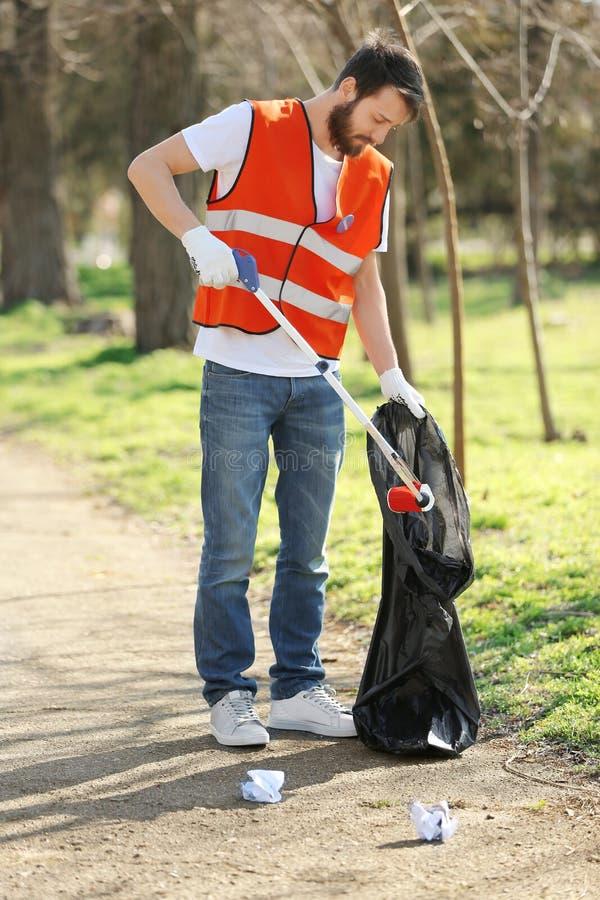 拾起废弃物的年轻人志愿者 库存照片