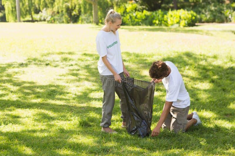 拾起废弃物的志愿者在公园 库存图片
