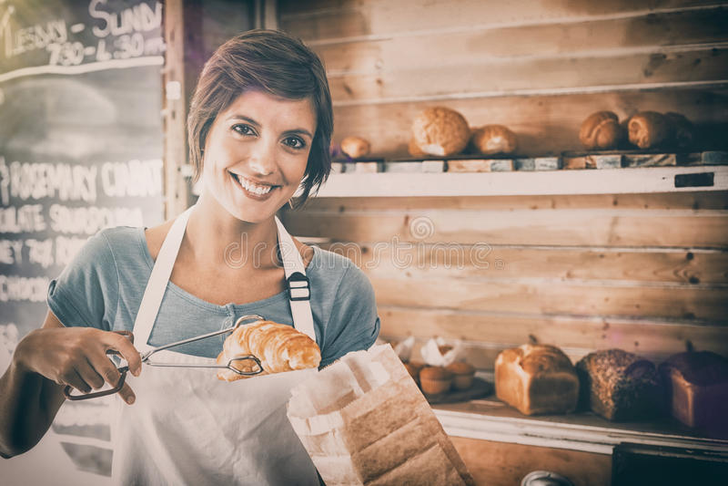 拾起新月形面包的俏丽的女服务员 免版税库存图片