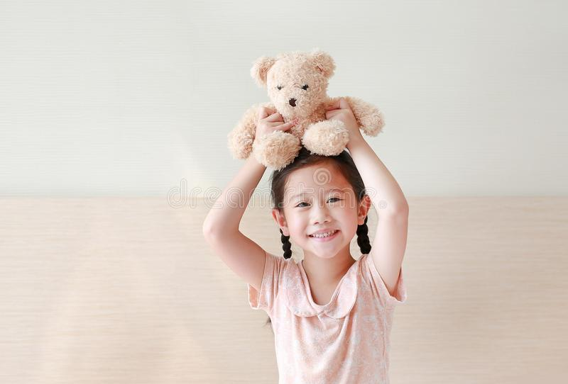 拾起棕色女用连杉衬裤的愉快的亚裔女孩涉及她的头,当在家时坐床 库存图片