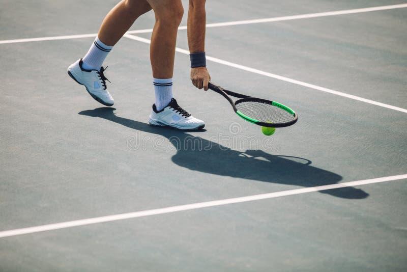 拾起球的网球员 库存图片