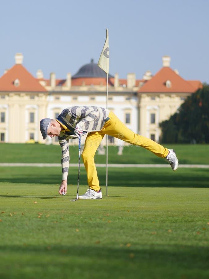 拾起球的高尔夫球运动员 库存照片