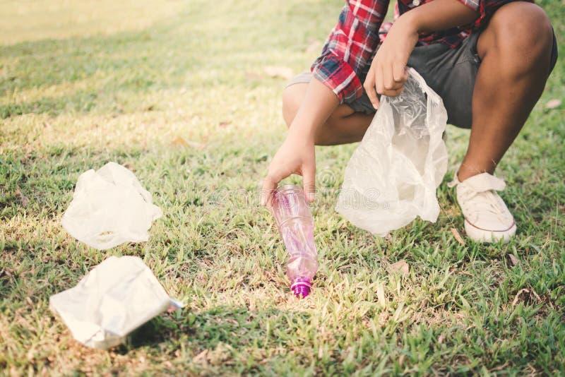拾起空在公园的瓶塑料的男孩 库存照片