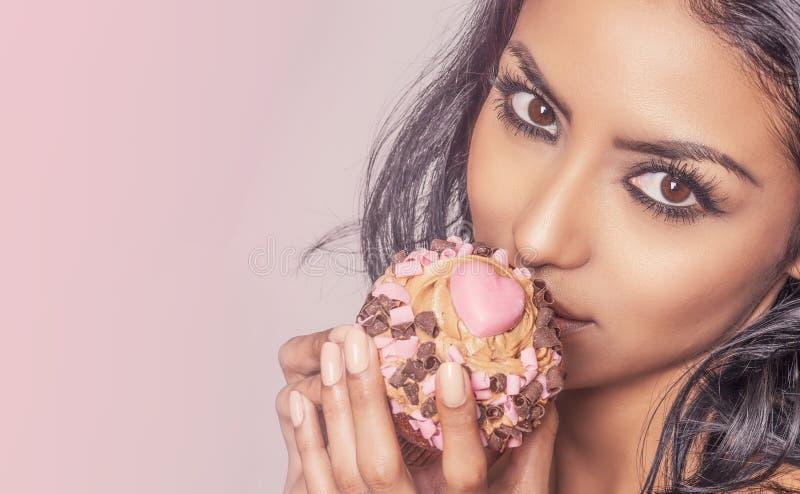 拿巧克力杯蛋糕的美女 库存照片