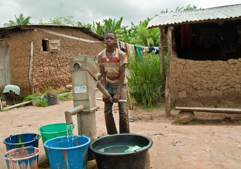 拿来水的非洲农村十几岁的男孩 免版税库存照片