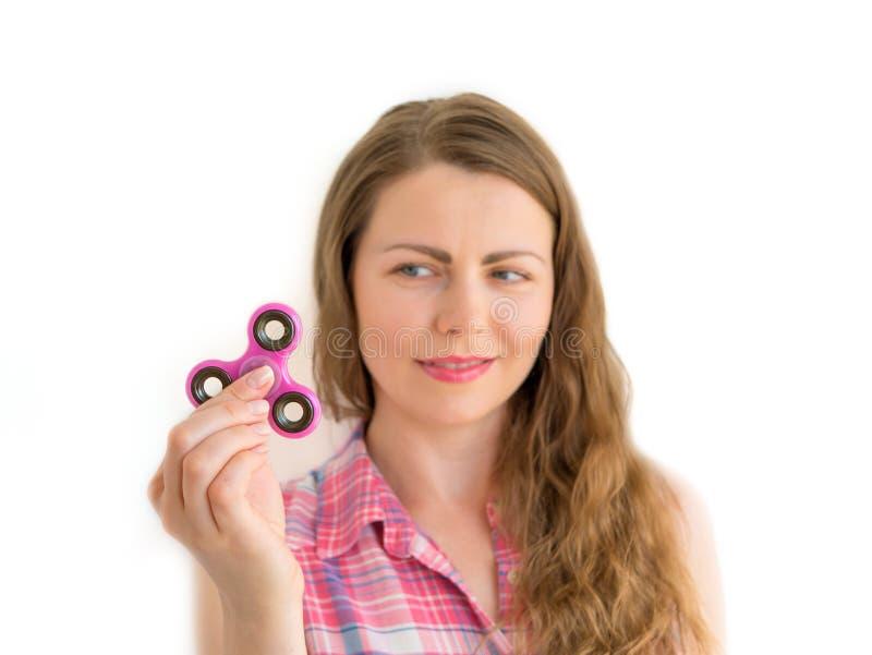 拿着一个五颜六色的手坐立不安锭床工人玩具的女孩 库存图片