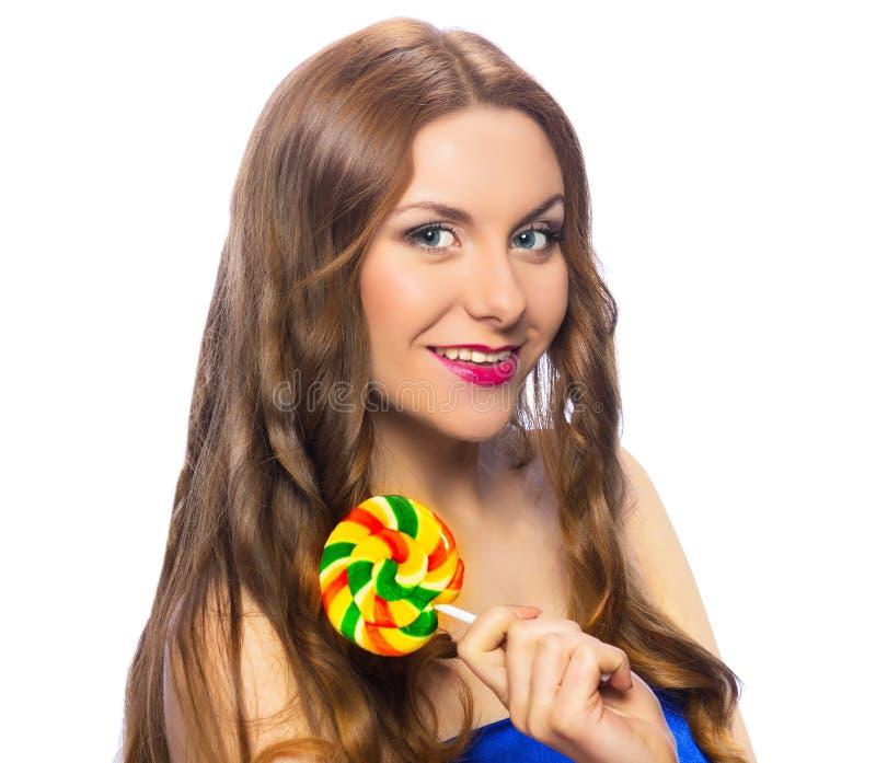 拿着一个五颜六色的扭转的棒棒糖的美丽的嬉戏的女孩 库存照片