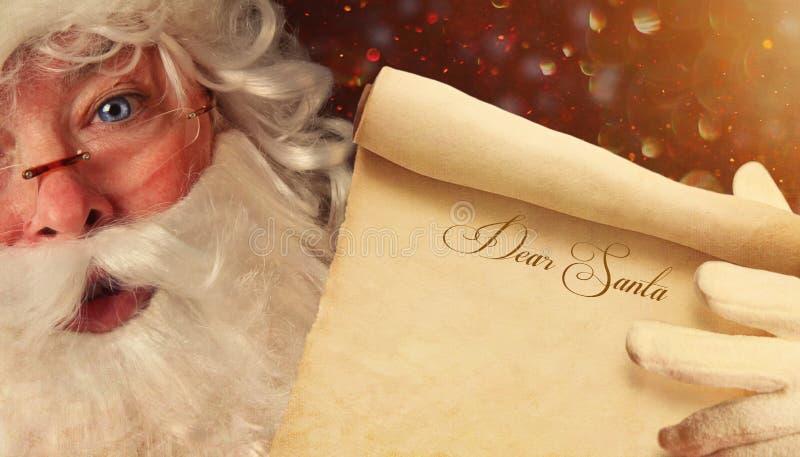 拿着一个亲爱的圣诞老人纸卷的圣诞老人特写镜头 图库摄影