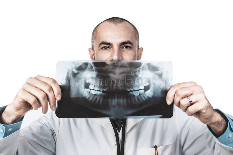 拿着一个全景X-射线的牙医医生的滑稽的画象 库存照片