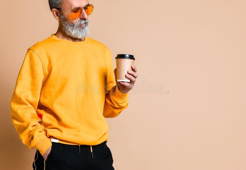拿着一个加奶咖啡杯子和看照相机的射击一个快乐的前辈 库存图片