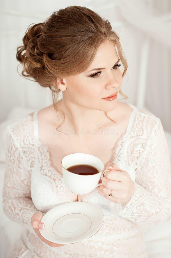 拿着一个加奶咖啡杯子的女孩 在一件白色外套 咖啡在床上 早晨从咖啡开始 免版税库存图片