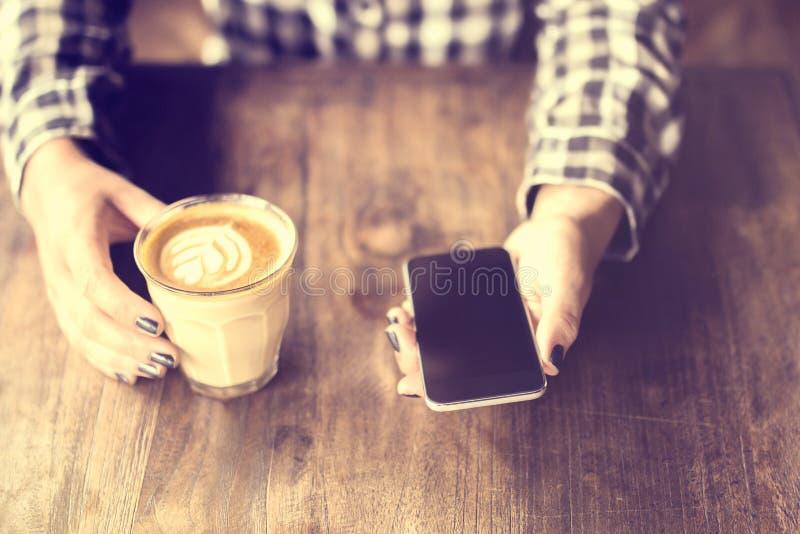 拿着一个咖啡和手机在木桌上的行家女孩 免版税图库摄影