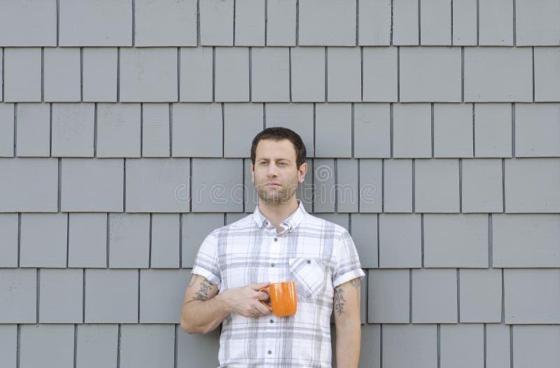 拿着一个咖啡杯有灰色中立背景的千福年的人 免版税库存图片