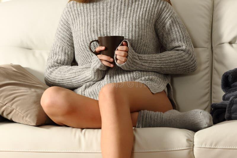 拿着一个咖啡杯的夫人热化在冬天 免版税库存图片