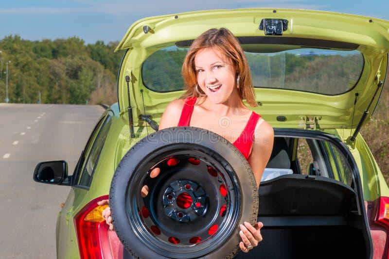 拿着一个备用轮胎的一个美丽的女孩的画象 图库摄影