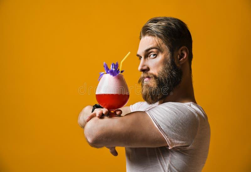 拿着一个多彩多姿的鸡尾酒的年轻人 免版税图库摄影