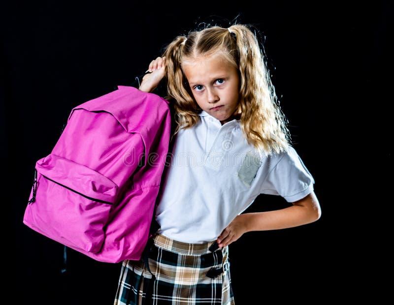 拿着一个大书包的不快乐的学校女孩在黑背景和家庭作业隔绝的有很多书回到学会dif的学校 库存照片