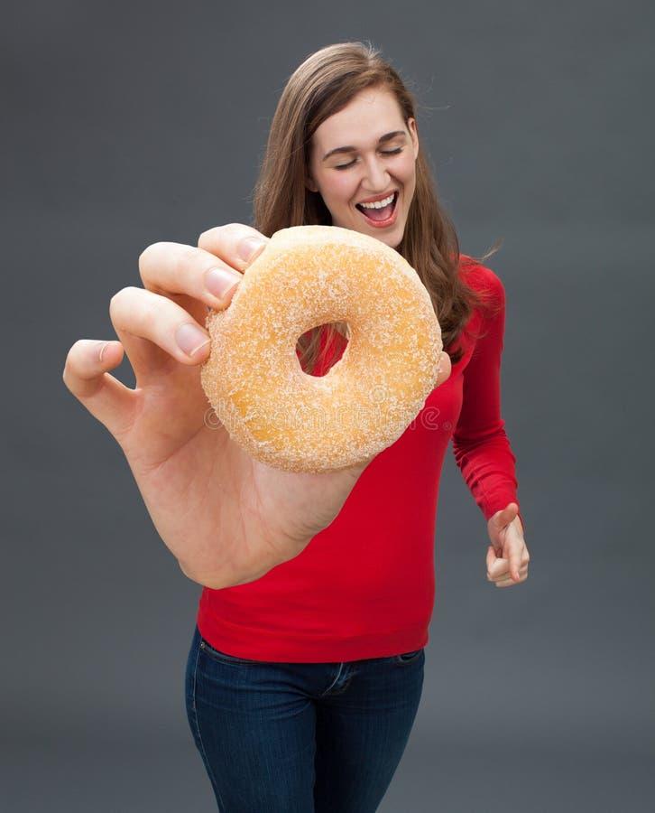 拿着一个大开胃多福饼的快乐的美丽的妇女作为诱惑 免版税库存照片