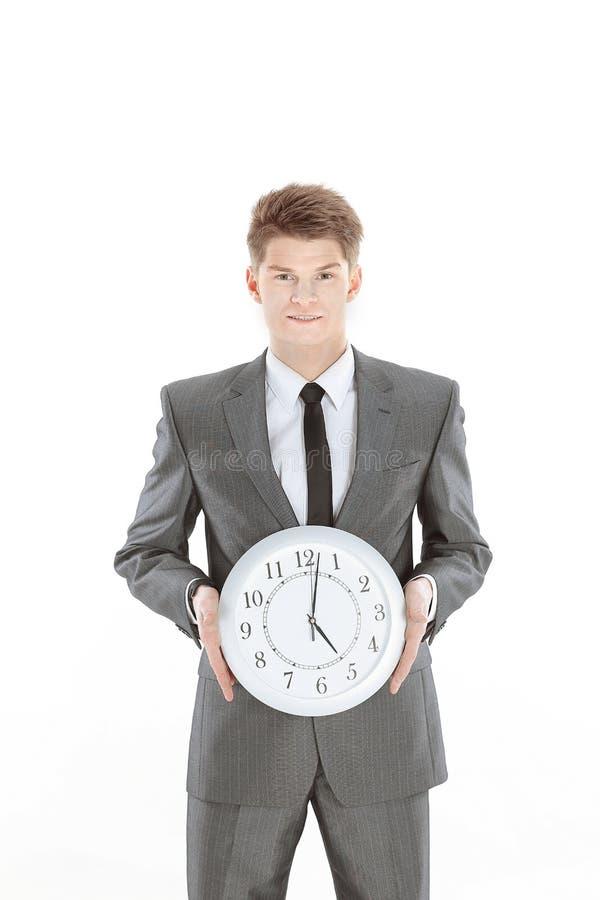 拿着一个大时钟的英俊的商人 笤帚查出的白色 免版税库存图片