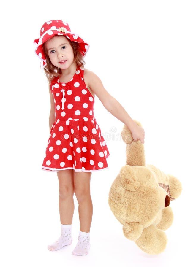 拿着一个大爪子玩具熊的小女孩 免版税库存照片