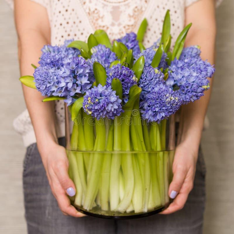 拿着一个大玻璃花瓶的妇女有很多新鲜的风信花在她的手上 图库摄影
