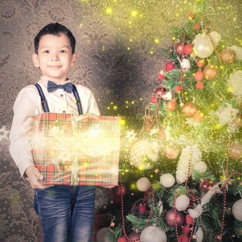 拿着一个大礼物盒的愉快的multiraceal男孩在圣诞节 免版税图库摄影