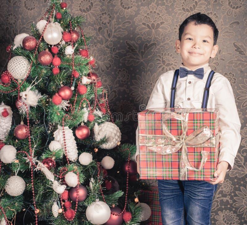 拿着一个大礼物盒的愉快的multiraceal男孩在圣诞节 库存照片