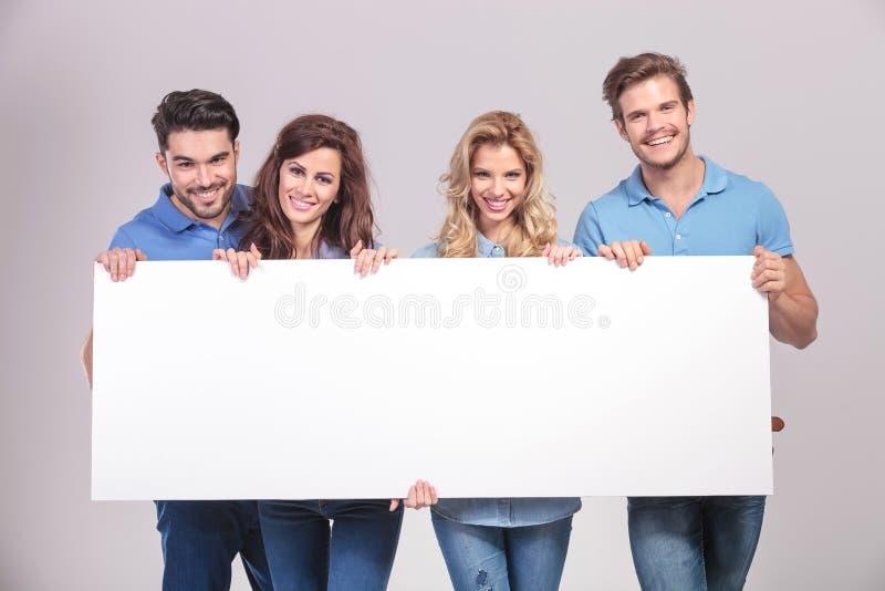 拿着一个大空白的委员会的偶然小组青年人 库存图片