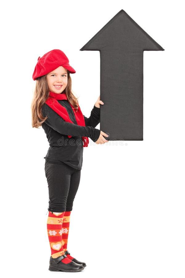 拿着一个大箭头的时兴的小女孩 图库摄影