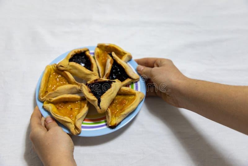 拿着一个套色板用Hamantash普珥节蓝莓和杏子在白色桌布的果酱曲奇饼的妇女手 免版税库存照片