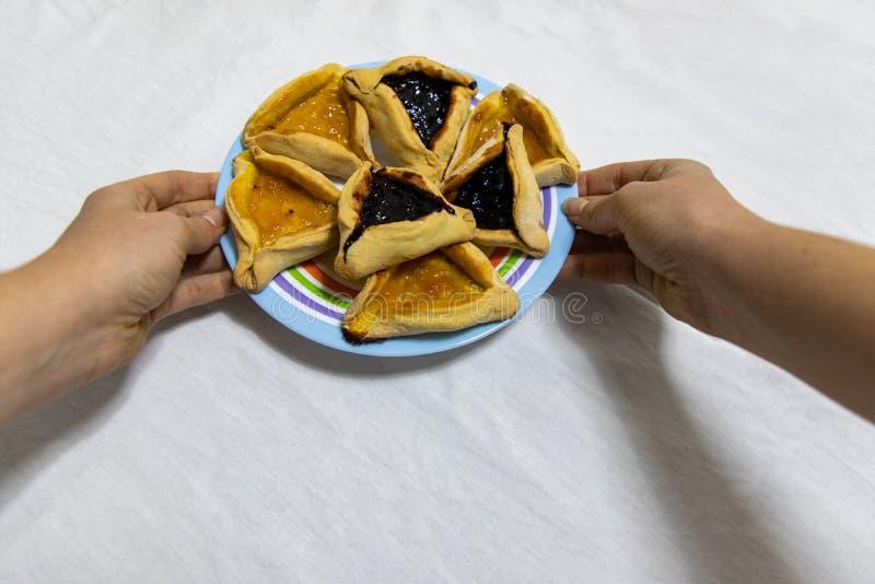 拿着一个套色板用Hamantash普珥节蓝莓和杏子在白色桌布的果酱曲奇饼的妇女手 免版税库存图片