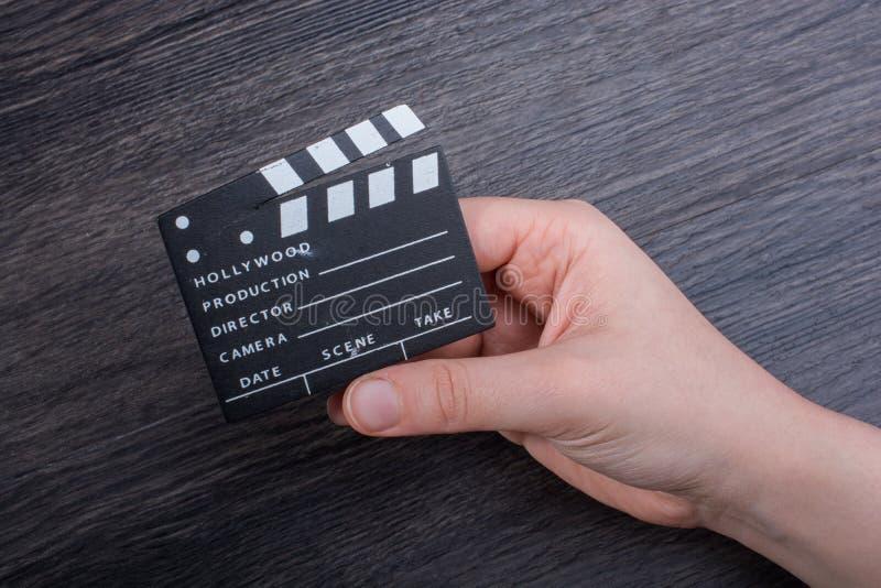 拿着一个小的电影拍板的手手中 免版税库存照片