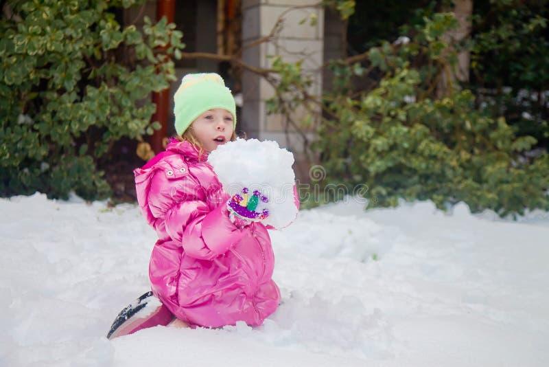 拿着一个巨大的雪球的逗人喜爱的白肤金发的女孩 库存照片