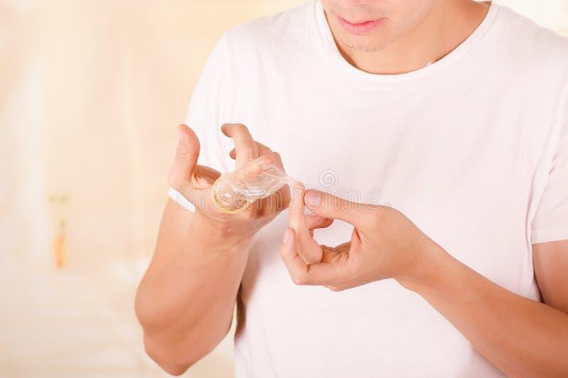 拿着一个开放打破的避孕套单手在他的面孔前面的和接触残破的片断的担心的人画象 库存图片