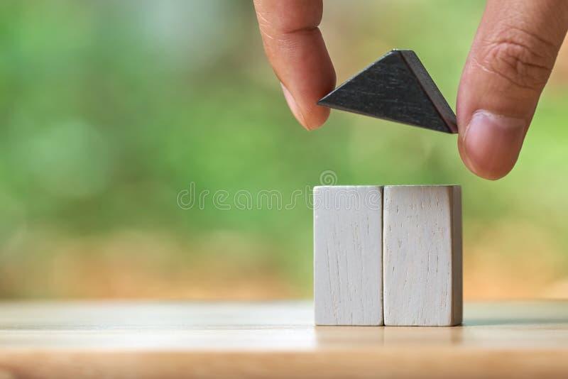 拿着一个式样房子模型的商人在堆被安置硬币 使用作为背景企业概念和房地产概念 免版税图库摄影