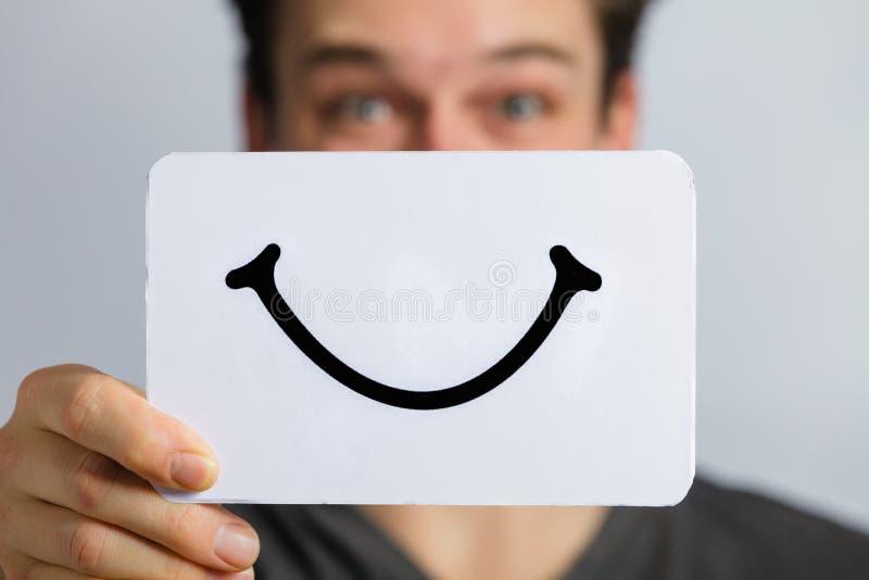 拿着一个微笑的心情委员会的某人的愉快的画象 库存照片
