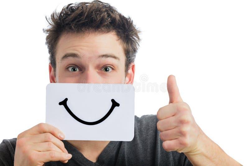 拿着一个微笑的心情委员会的某人的愉快的画象 免版税库存图片