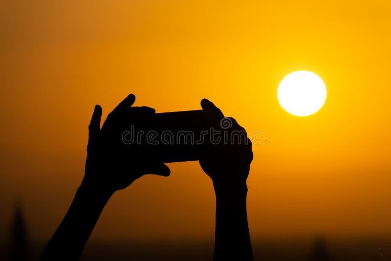 拿着一个手机和做摄影的手剪影巨大的太阳在日落或日出期间 免版税图库摄影