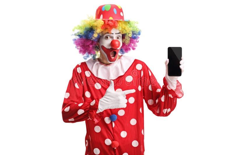 拿着一个手机和指向它的快乐的小丑 免版税图库摄影