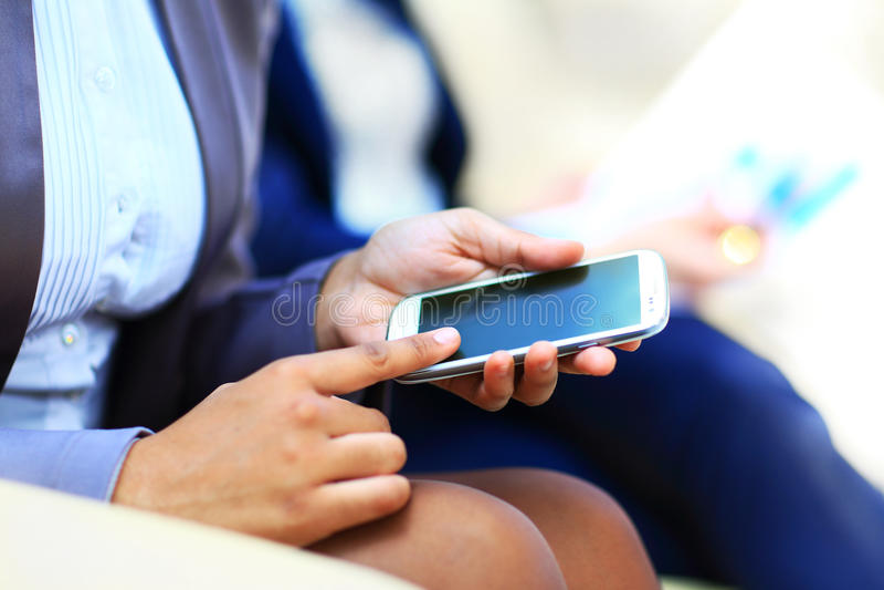 拿着一个手机的妇女手 免版税库存图片