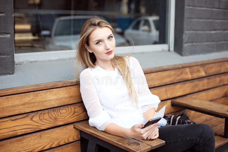 拿着一个手机的年轻美丽的白肤金发的妇女,当坐与在咖啡馆内部时的一本便携式的网络书 图库摄影