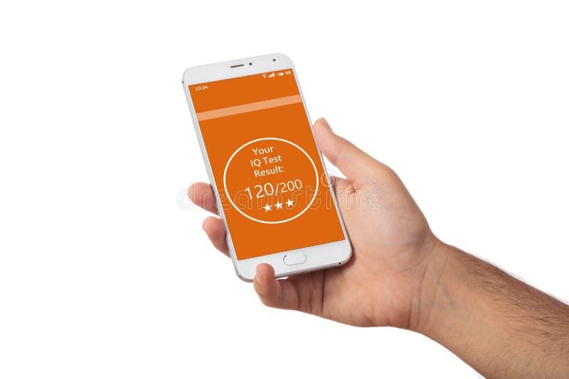 拿着一个手机,在屏幕上的智商考试成绩的人手,反对白色 免版税库存图片