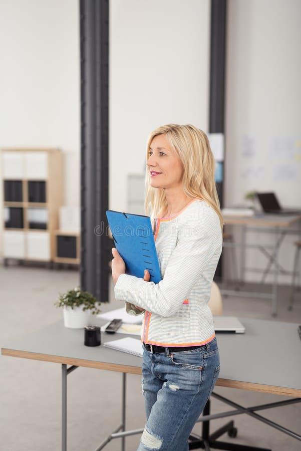拿着一个文件夹的女性雇员在办公室 图库摄影