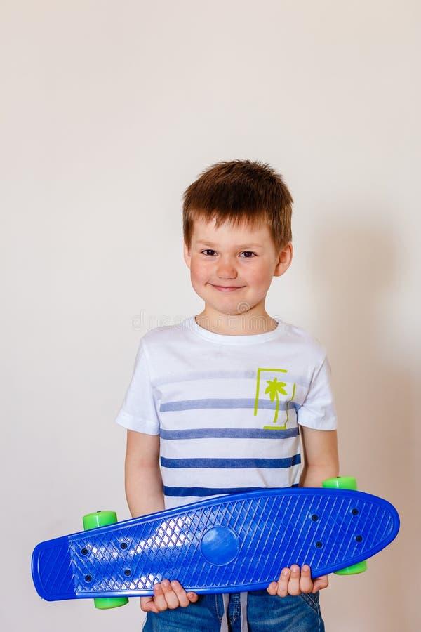 拿着一个新的蓝色滑板的逗人喜爱的微笑的五岁的孩子 免版税库存照片