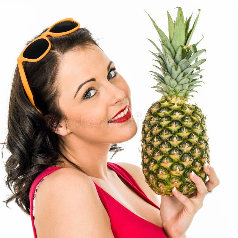 拿着一个新鲜的成熟菠萝的妇女 库存图片