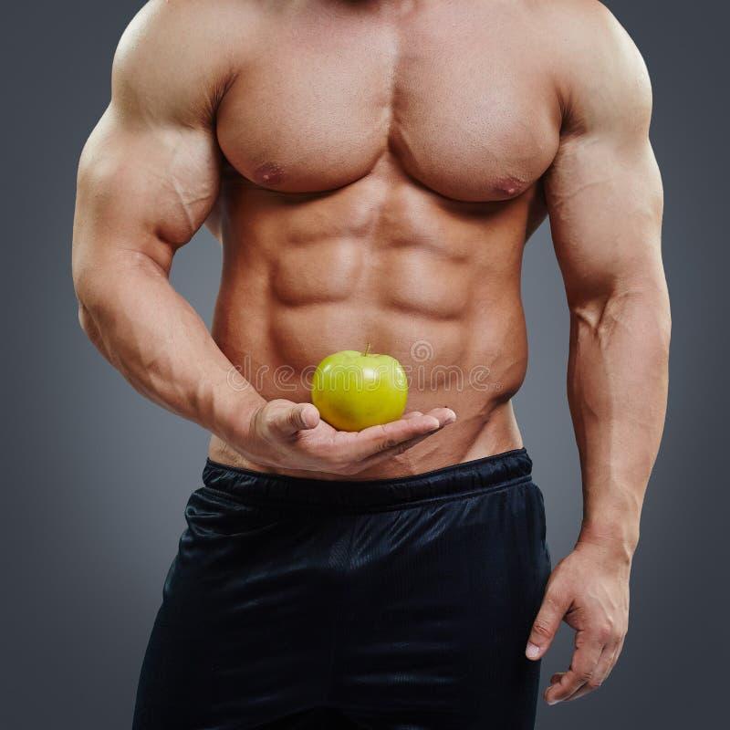 拿着一个新鲜的苹果的赤裸上身的肌肉人 库存照片